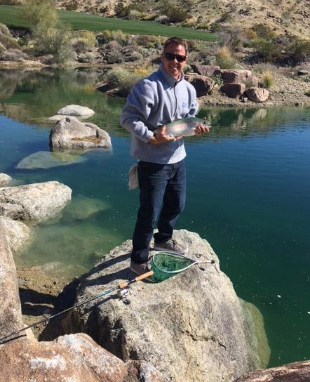 chris beaty on rock holding a caught fish